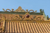 Photo Dragon sculpture on rooftop of Chinese temple in Hong Kong, China. The Chinese character on rooftop means Taoism.