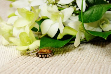 Bouquet with white and green orchids and beautiful wedding rings.