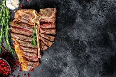 Grilled T-bone steak. Cooked tbone beef. Black background. Top view. Copy space.