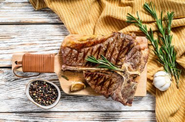 Grilled T bone steak on a chopping Board. Cooked tbone beef. White wooden background. Top view.