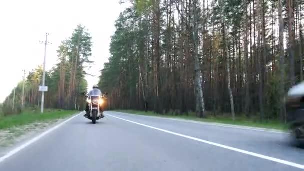 Motorkářka v přilbě na motorce po lesní cestě při západu slunce