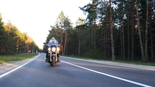 adult biker without helmet rides a motorcycle along a forest road at sunset