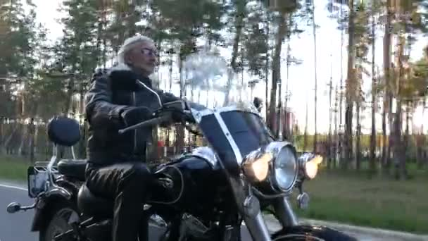 felnőtt biciklis sisak nélkül lovagolni egy motorkerékpár mentén erdei úton naplementekor