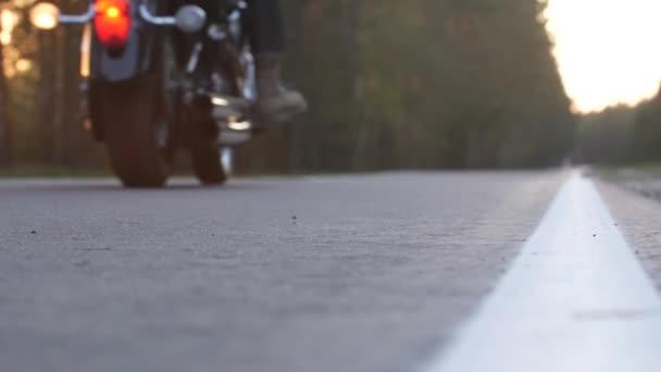 Biker pro dospělé bez přilby na motocyklu po lesní cestě při západu slunce