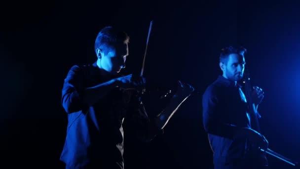 duó a fiatal zenészek játszott az elektromos cselló és elektromos hegedű fekete háttér, elszigetelt