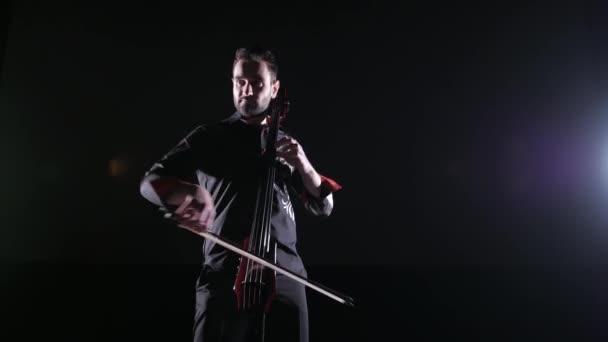 fiatal jóképű férfi játszik elektromos cselló fekete háttér, elszigetelt