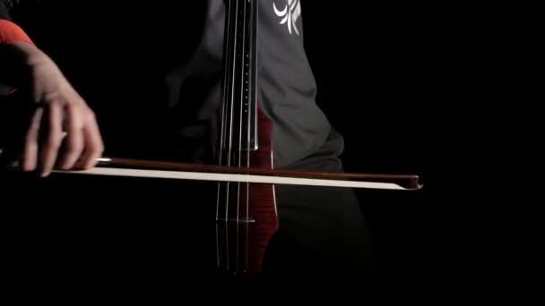 Hand eines Mannes, der ein elektrisches Cello auf schwarzem Hintergrund spielt, Nahaufnahme von Saiten, Bogen und Griffbrett, isoliert
