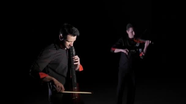 Duett junger Männer, die elektrisches Cello und elektrische Geige auf schwarzem Hintergrund spielen, isoliert