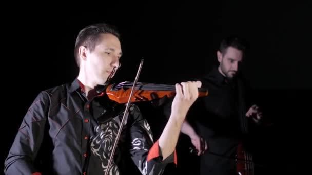 Duet mladých mužů s elektrickými violoncello a elektrickými housle na černém pozadí, izolovaný
