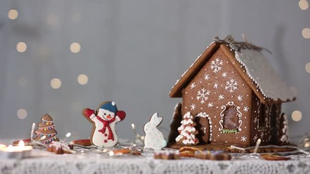 Handmade mézeskalács ház a háttérben a csillogó fények, hóember figurák és a karácsonyfa