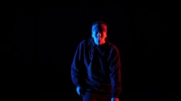 Mladá krásná dívka tančí hip hop, freestyle, pouliční tanec v ateliéru na černém pozadí, izolovaný