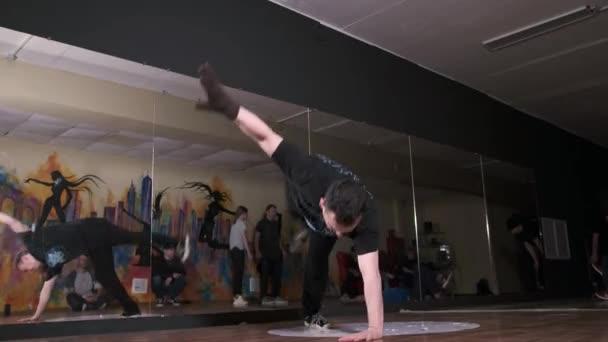 Videó egy aktív fiatalemberről, aki hip-hop koreográfiát táncol és megtörik. Más táncosok állnak a közelben. Tánciskola. Fogalma javítása break tánc technika. Ifjúsági szubkultúra. Kortárs koreográfia. Lassú mozgás.