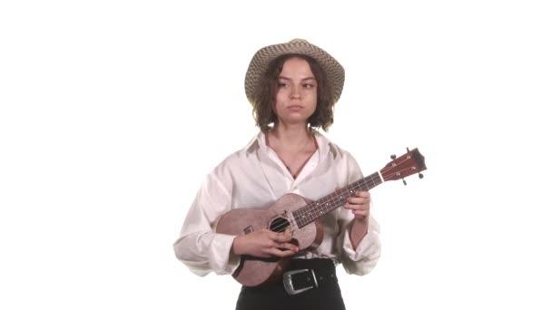 Hezká dívka v bílé blůze a klobouku hraje ukulele. Izolovaný. Středně dlouhý úder