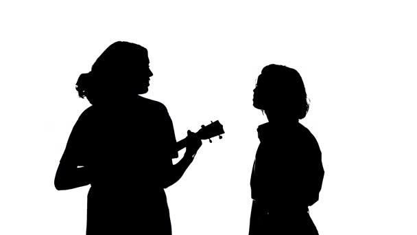 Střední šance na duet mladých talentovaných dívek zpívajících a hrajících ukulele. Tvůrčí duet koncept. Černá silueta na bílém pozadí