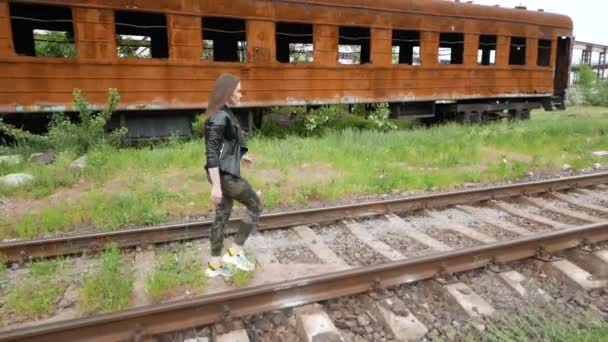 Attractive girl in a black jacket walking along the abandoned railway tracks. Old train on background. Slow motion.