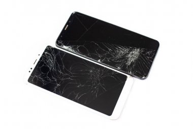 two broken phones of white and black on a white background. cracked touchscreen glass of the touch screen isolate