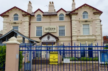 New Brighton, UK: Jun 3, 2020: A street view shows the impact of Corona virus pandemic on businesses which are required by law to close temporarily. Entrance gates closed at Queen's Royal Hotel.