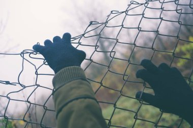Gloved Hands on Wire Fence on an Overcast Day Closeup