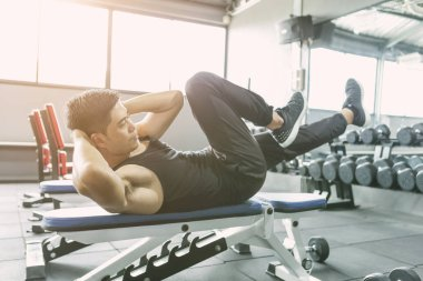 Young man making exercise, sit-ups and cross crunches for abs muscles, training workout in fitness club or gym.