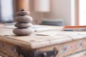 Feng Shui: Stone cairn v popředí, rozmazaný obývací pokoj v pozadí. Bilance a relaxace.