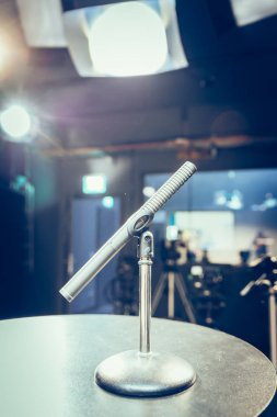Metal microphone in the studio, studio lights in the blurry background