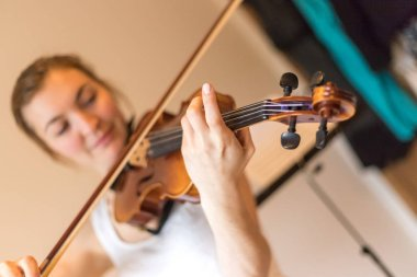 Pretty young girl practices on her violin, acoustic music