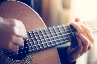 Musician plays a classical guitar, blurry hands, fretboard and fingers