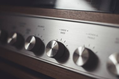 Control knops of silver wooden vintage amplifier, closeup