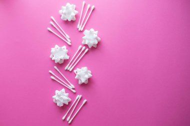 Spa concept. Facials skin care. Cotton buds with white flowers on the pink background.
