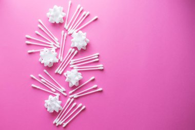 Spa concept. Facials skin care. Cotton buds with white flowers on the pink background. flat lay. copy space