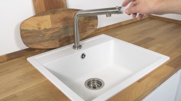 Kézi nyitás vízcsap fehér mosogatóval a konyhában.