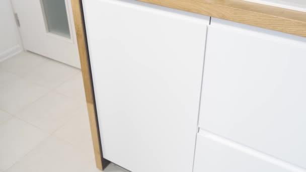 offene Spülmaschine mit Geschirr in der weißen Küche mit Holzplatte.