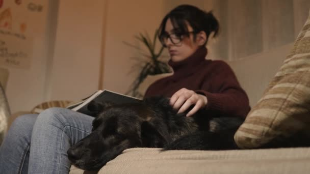 A girl is sitting on a sofa reading a big book. A black dog is next to her also on the couch.
