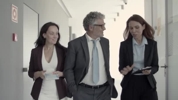 Cheerful successful business people talking while walking