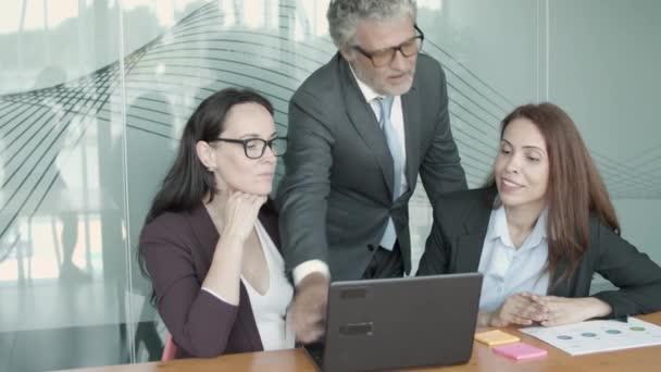 Usmívající se výkonný ředitel v brýlích ukazuje na notebook a vysvětluje detaily