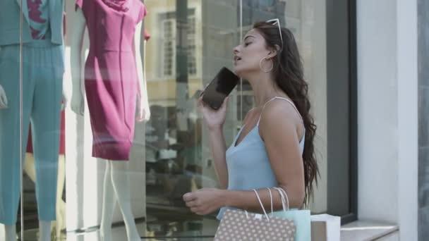 Barna nő beszél a mobiltelefon és nézi bolt ablak