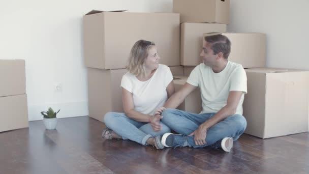 Fröhliches Paar sitzt in der Nähe von Kisten auf dem Boden