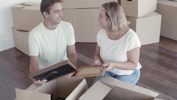 Glückliches Paar beim Packen von Dingen für den Umzug