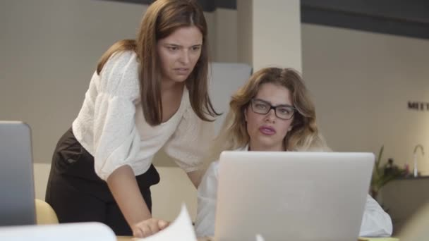 Female professionals sitting and standing at table with laptop