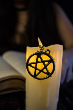 Beş köşeli yıldız bir mum ve bir kitap üzerinde