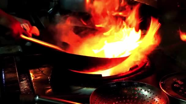 Chef stir food in restaurant kitchen at stove with pan doing flambe on food