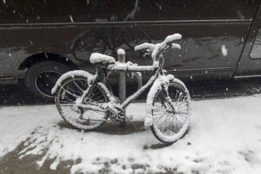 Bicycle covered in snow parked near a van on the sidewalk of urb
