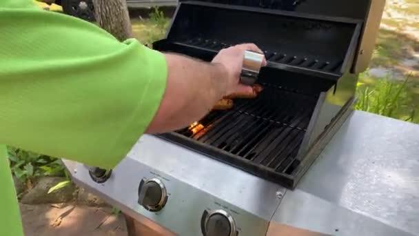 Životní styl léto venkovní muž vaření kůly a klobásy na propan plyn gril duté kovové jazyky