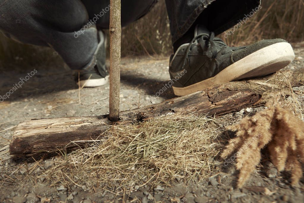 Man in hat trying to make a fire with wood stick friction