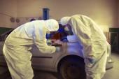 Fotografia Del crimine - lo sviluppo delle impronte digitali su sospetta auto nel garage di polizia sotto la luce Uv
