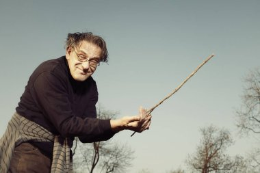 Man in ugly style dress practicing in dowsing with rods