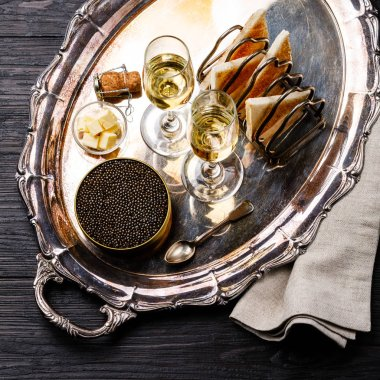 Black caviar in can, fresh bread toast and champagne on silver tray on black wooden background