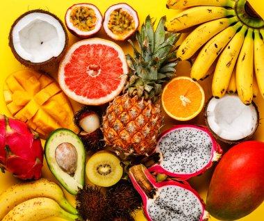 Tropical exotic fruits assorted Pineapple, Coconut, Pitahaya, Kiwi, Banana, Mango, Orange, Avocado, Passion Fruit on yellow background