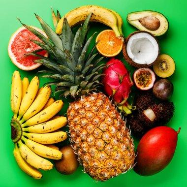 Tropical exotic fruits assorted Pineapple, Coconut, Pitahaya, Kiwi, Banana, Mango, Orange, Avocado, Passion Fruit on green background