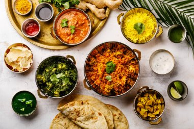 Indian food Curry butter chicken, Palak Paneer, Chiken Tikka, Biryani, Papad, Dal, Rice with Saffron and Naan bread on white background
